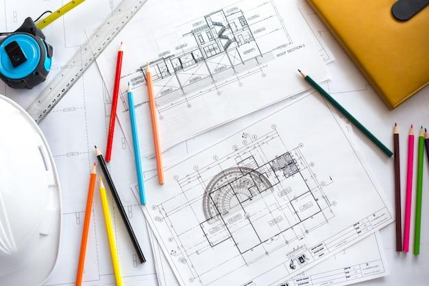 Изображение чертежей с карандашом уровня и каской на столе