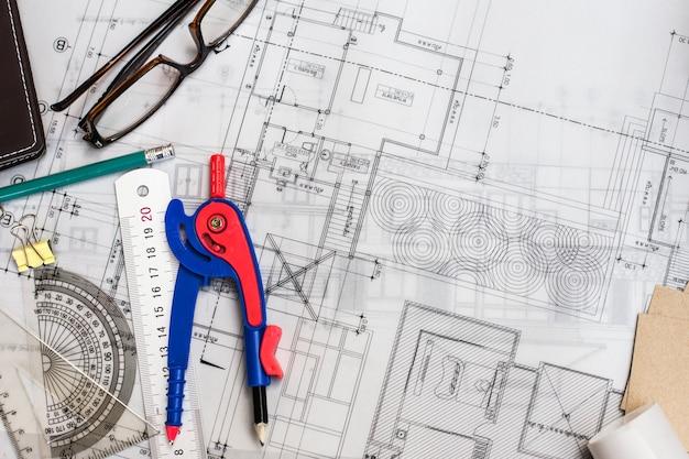 鉛筆、ルーラー、テーブル上のメガネ、レトロエフェクト付きのテーブル上の建設計画図