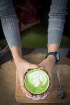 女性の手で抹茶緑茶のカップ。