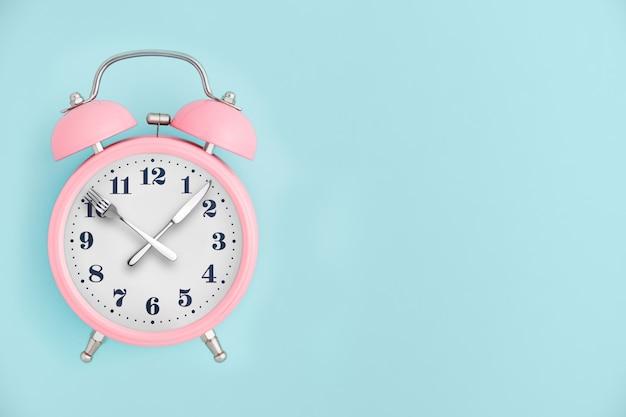目覚まし時計。時計の針の代わりにフォークとナイフ。