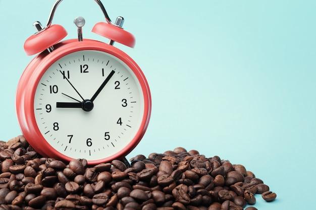 Красный будильник стоит в куче кофейных зерен