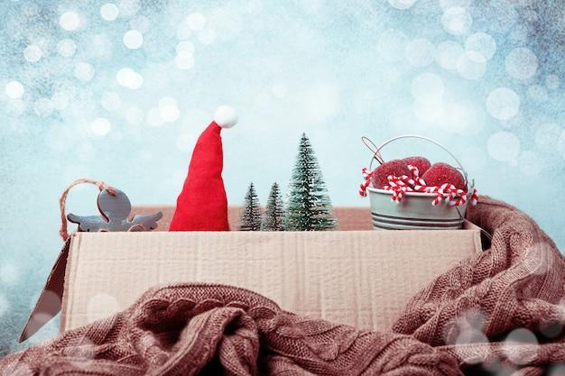 クリスマスの装飾。オープンボックス、サンタさんの帽子、小さなクリスマスツリー、クリスマスのおもちゃのバケツ、ニットブランケット。