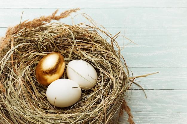 Одно золотое и два обычных яйца в гнезде сена