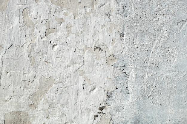 古いひびの入った石膏壁、白いテクスチャ背景