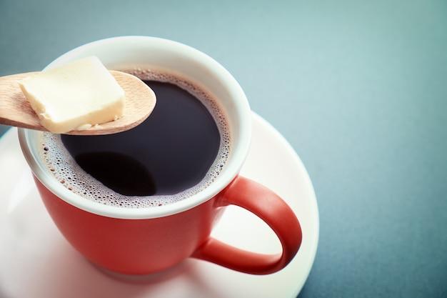 スプーンの防弾コーヒー、カップ、バター