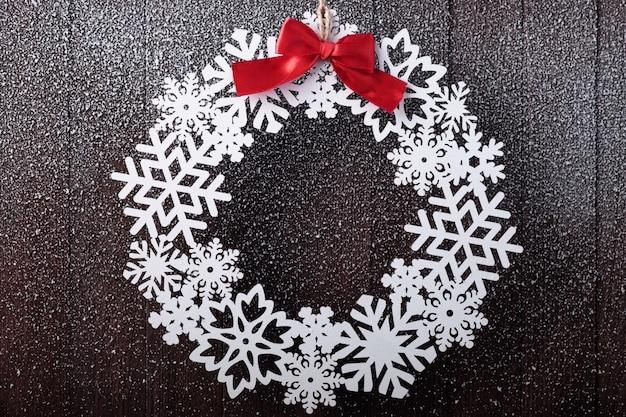 赤の弓と雪の木製のクリスマスリース。にわか雪