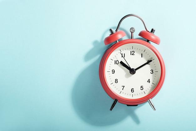 青の上に横たわる影と赤い目覚まし時計。上からの眺め。