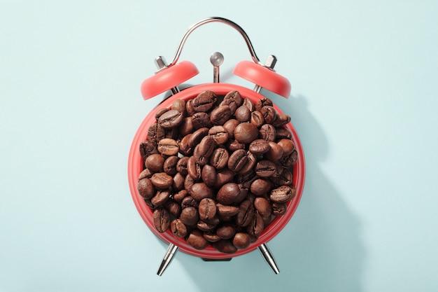 コーヒー豆で満たされた赤い目覚まし時計。朝の目覚め、営業日の始まりの概念