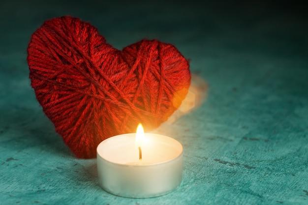 非常に熱い蝋燭の近くの赤いハート。バレンタインデー。火による温暖化