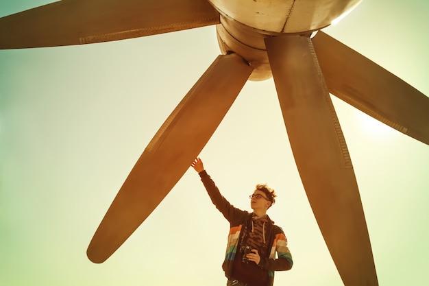 カメラを持つ少年が巨大な航空機のプロペラに触れる