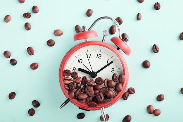 Красный будильник и жареные кофейные зерна на синем