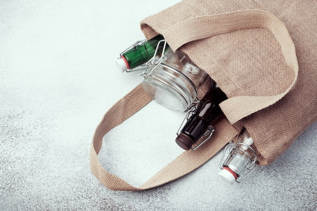 黄麻布の袋に入れた再利用可能なガラス瓶と瓶。持続可能なライフスタイル。廃棄物ゼロの食料品ショッピングコンセプト