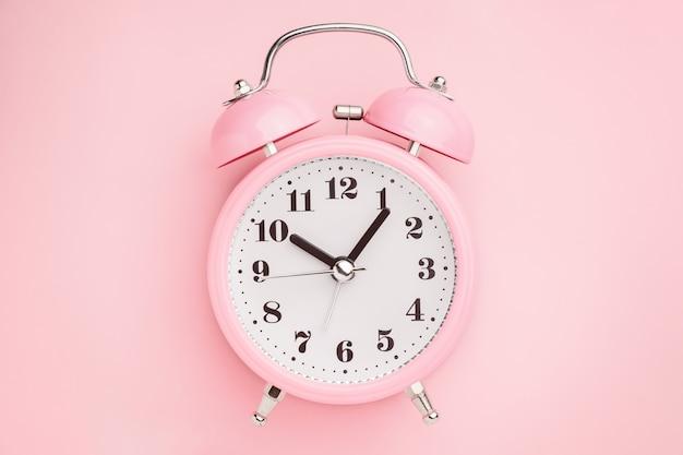 Розовый будильник на розовом столе. минимальный стиль