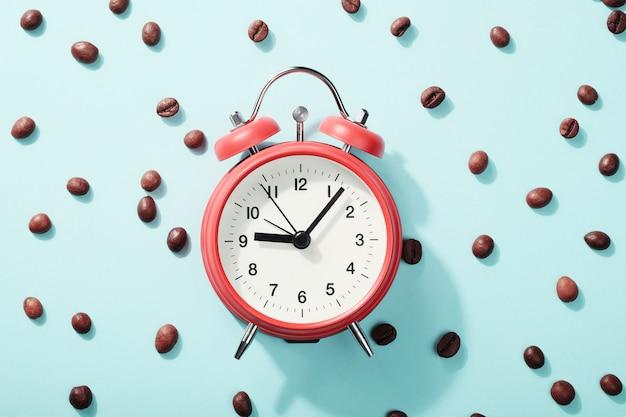 赤い目覚まし時計とローストコーヒー豆。朝の目覚め、営業日の始まりの概念