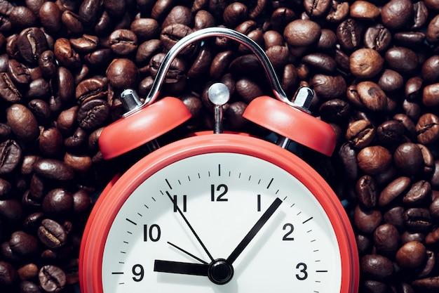Красный будильник лежа на кофейных зернах.