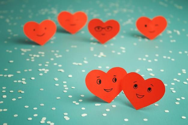 Многие красные улыбающиеся сердца на синем столе. день святого валентина. влюбленная пара.
