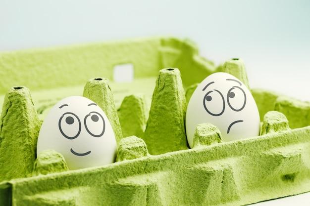 Два яйца с нарисованными лицами в зеленой яичной коробке. оптимист и пессимист