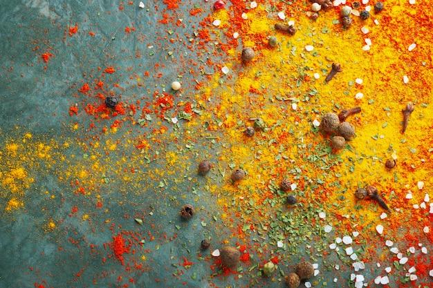 テーブルの上に散らばったさまざまなスパイス、赤いパプリカパウダー、ターメリック、塩、クローブ、コショウ