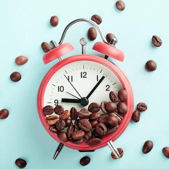 赤い目覚まし時計と青の背景にローストコーヒー豆。朝の目覚め、就業日の始まりのコンセプト