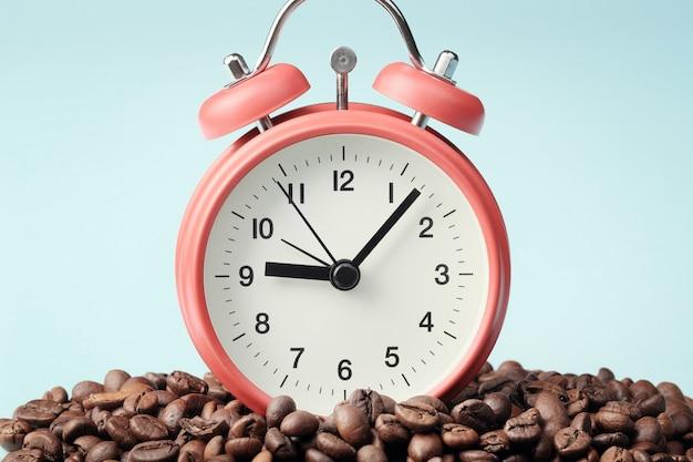 Красный будильник стоя в куче кофейных зерен. концепция утреннего пробуждения, начало рабочего дня