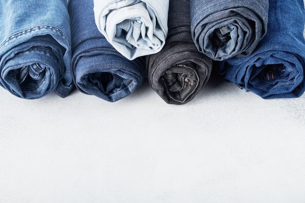 Стек различных проката джинсов на белом фоне