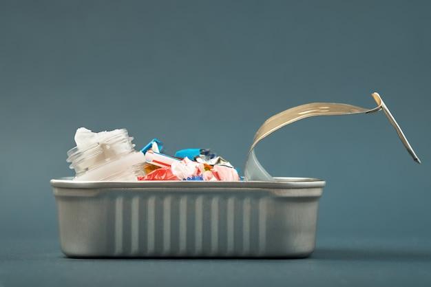 Открытая консервная банка. пластиковые отходы вместо рыбы внутри. концепция пластического загрязнения океана