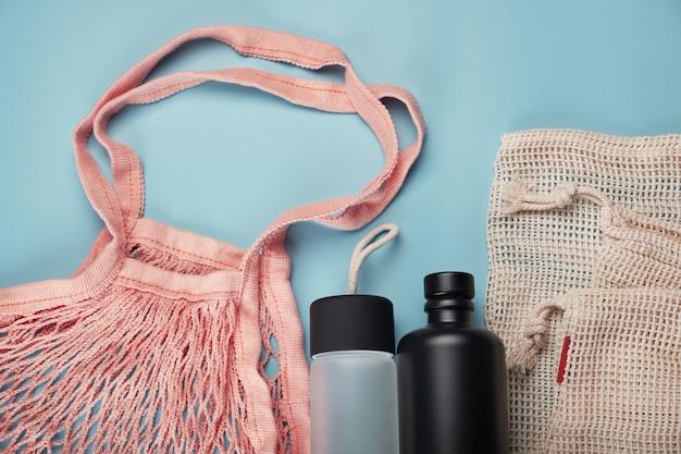 Хлопок эко сумки и бутылки с водой на синем фоне. ноль отходов концепция