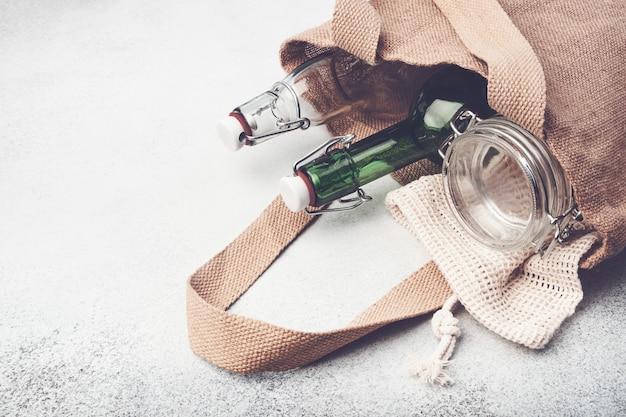 黄麻布の袋の再利用可能なガラスビンそして瓶。持続可能なライフスタイル。無駄のない食料品の買い物のコンセプト