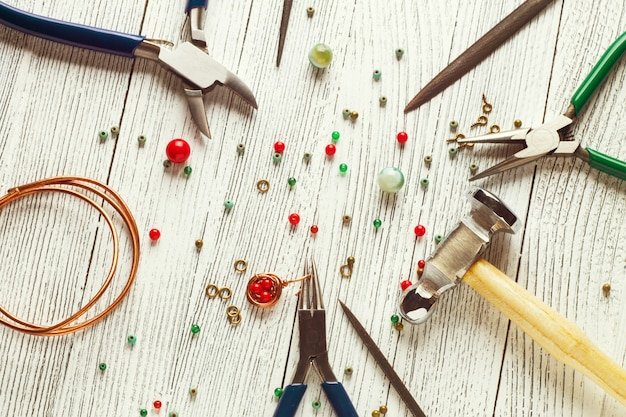 Разноцветные бусы, медная проволока и ювелирные инструменты. проволочная упаковка. вид сверху