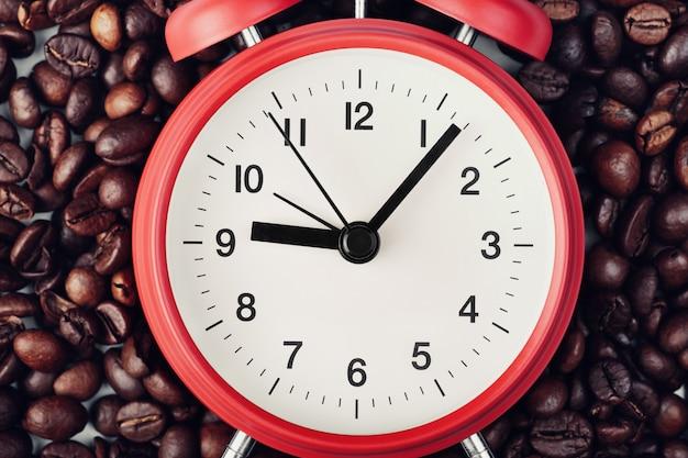 Красный будильник лежа на кофейных зернах. семь минут десятого на часах. концепция утреннего пробуждения, начало рабочего дня