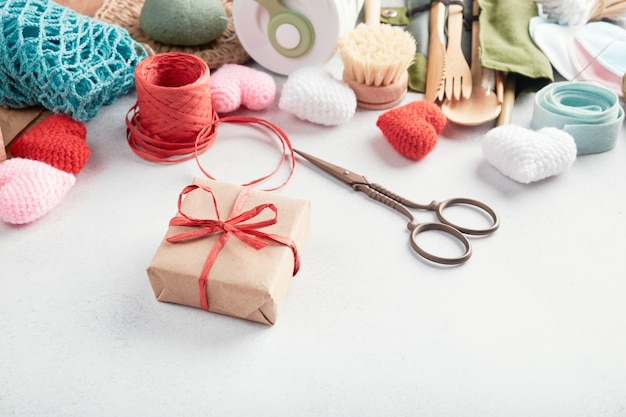 Набор эко подарков, разложенных на столе. нулевой подарок, завернутый в бумагу.