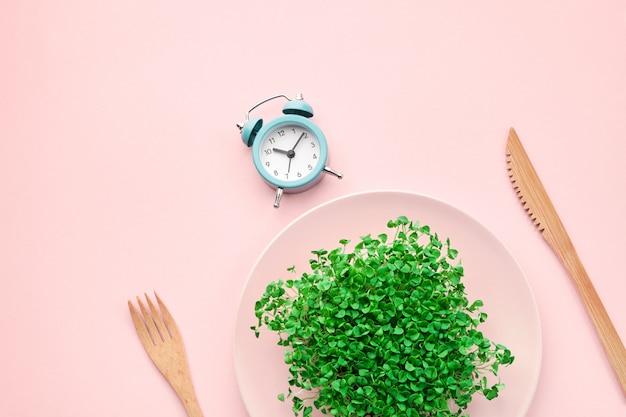 Будильник, столовые приборы и тарелка с зеленью на розовом