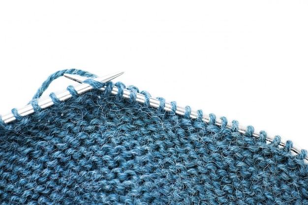編み針と白で隔離ニットウール生地。進行中の作業