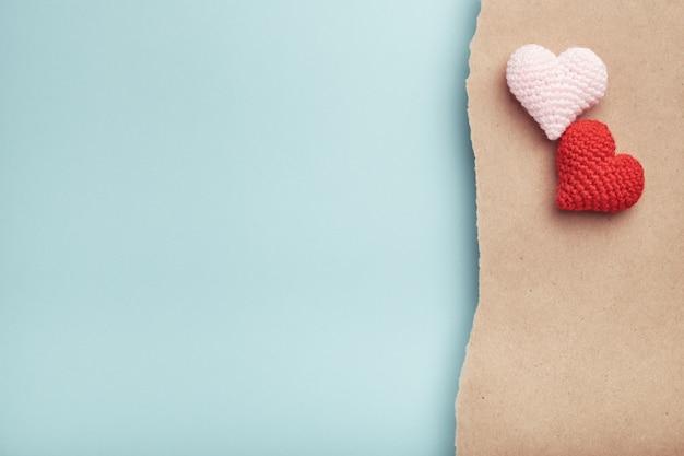 Два вязаных сердца ручной работы на рваной крафт-бумаге