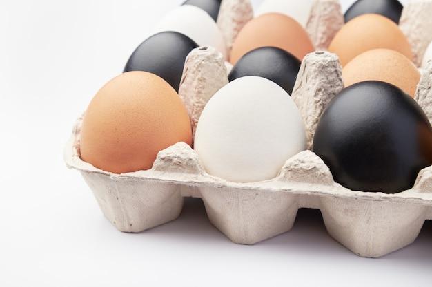 Яйца разных цветов в картонных коробках