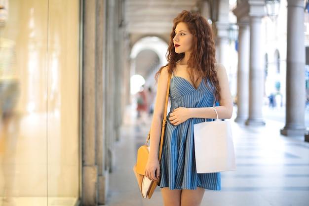 通りを歩いて、ショーケースを見て若い女の子