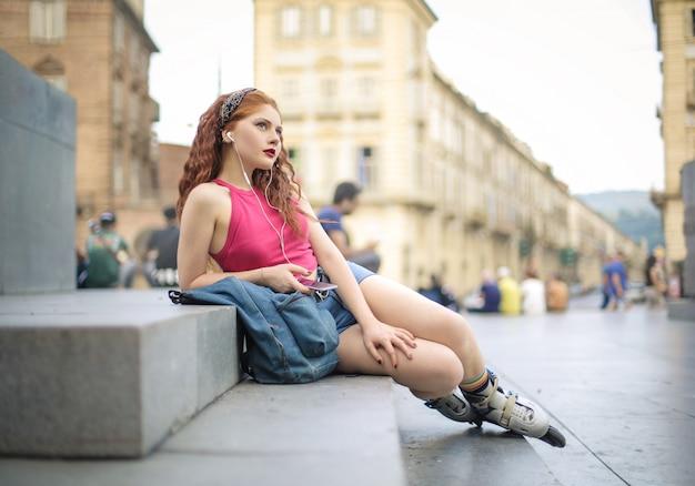 Классный подросток сидит на улице, слушает музыку