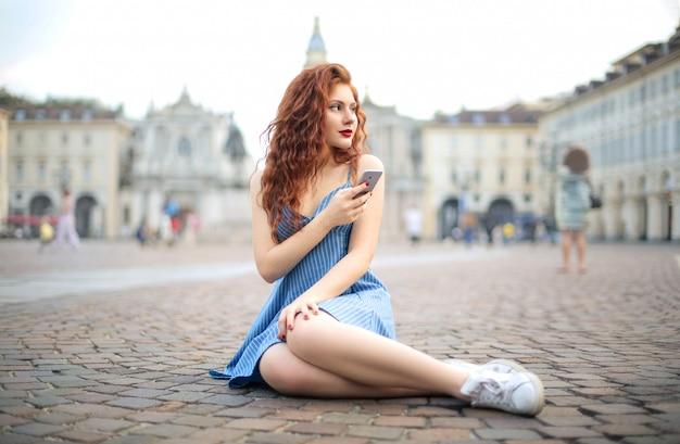 広場に座って、彼女のスマートフォンをチェックする美しい少女
