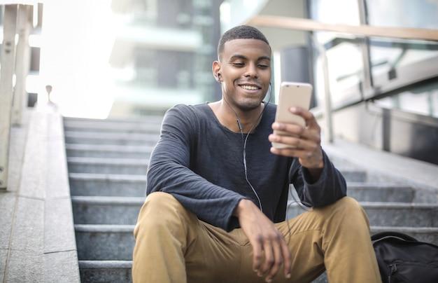Парень сидит на лестнице, смотрит свой телефон и смеется