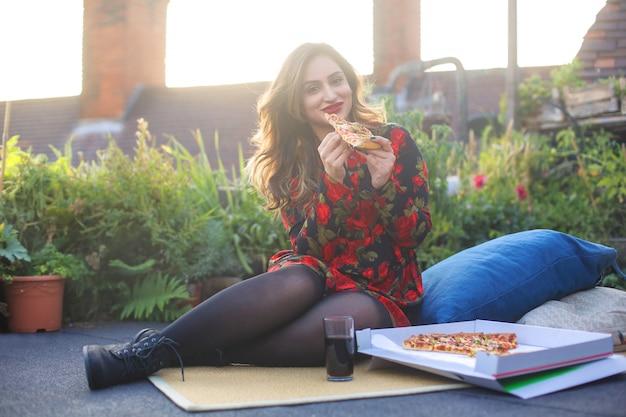 Девушка наслаждается ужином с пиццей на террасе