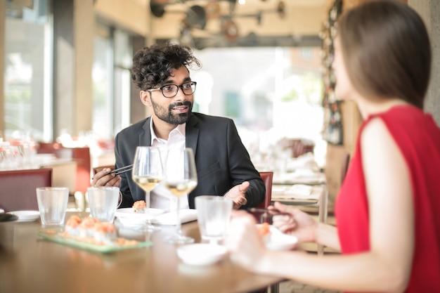 Друзья веселятся, едят вместе в элегантном ресторане
