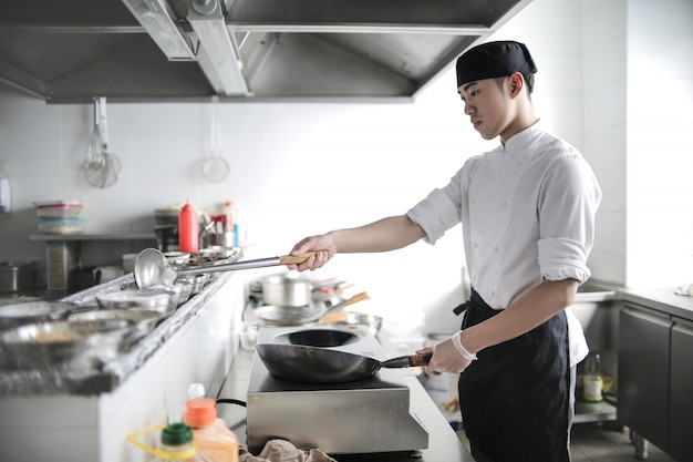 レストランのキッチンで料理をする中国人シェフ