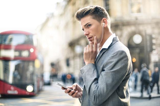 通りを歩きながら電話で呼び出しを持つハンサムなビジネスマン