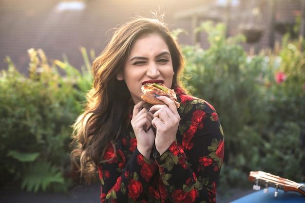 Смешная девчонка ест пиццу на террасе