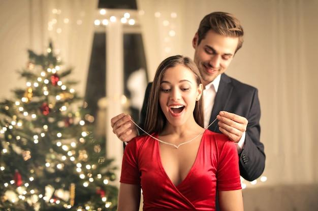 彼女のガールフレンドに美しいネックレスを贈る男
