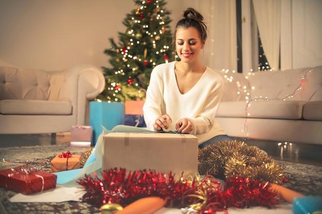 Девушка упаковывает рождественские подарки