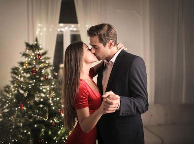 Прекрасная пара целуется дома, празднуя новый год