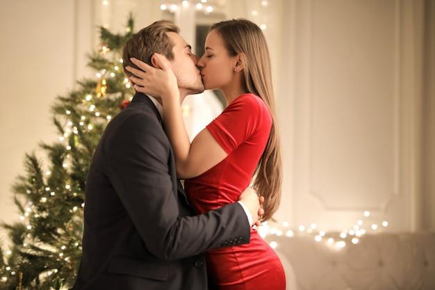 情熱的なカップルが彼らの家のクリスマスツリーの前でキス