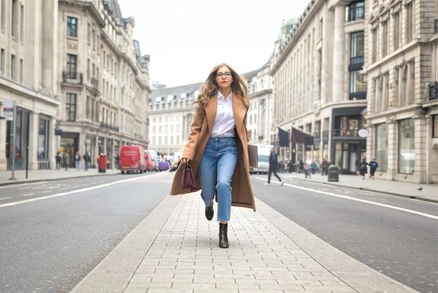 通りで走っているファッショナブルなビジネス女性