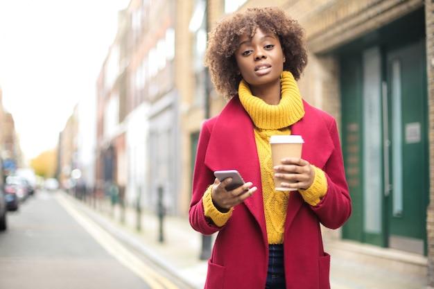 Модная девушка собирается на работу, пьет кофе